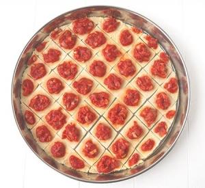 Ajout du coulis de tomate sur la pâte à pizza.