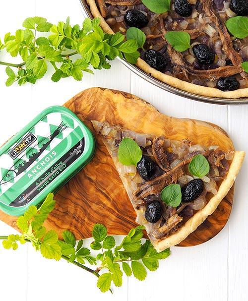 Présentation d'une part de pissaladière et une boite d'anchois