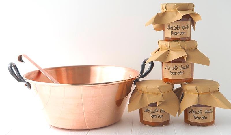 La bassine à confiture en cuivre avec ses pots de confiture d'abricots